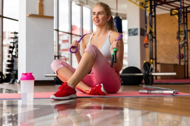 Mujer en polainas rosadas con saltar la cuerda