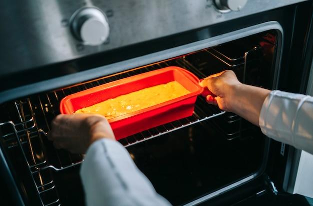Una mujer pone un bizcocho en el horno para hornearlo