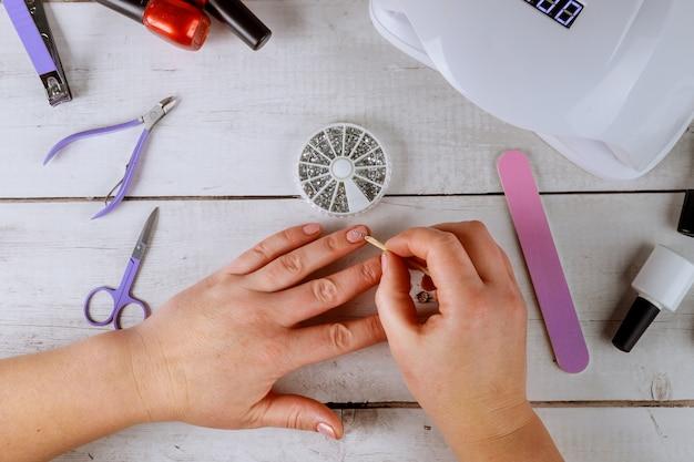 Mujer pone diamantes de imitación en las uñas fabricación de gel de manicura.