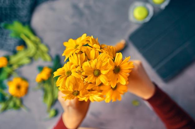 La mujer pone flores de crisantemo amarillas en un florero transparente de vidrio sobre la mesa del desván