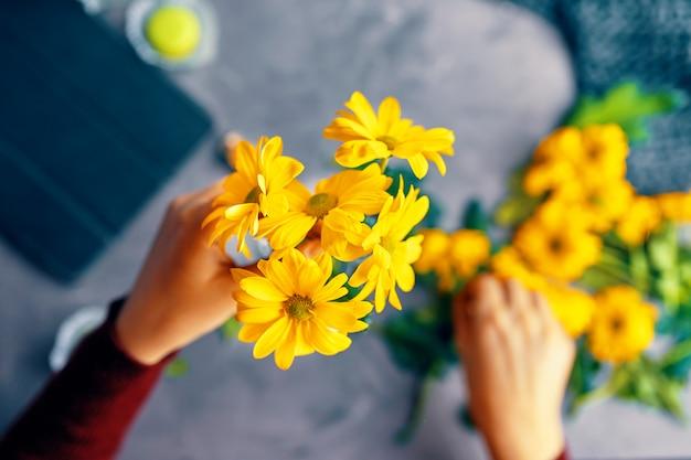 La mujer pone flores de crisantemo amarillas en un jarrón transparente de vidrio sobre la mesa del desván