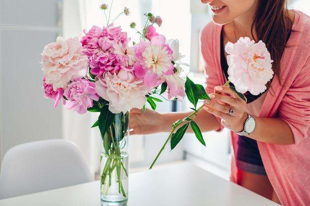Mujer pone flores de peonías en florero.