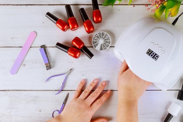 La mujer pone la mano en la lámpara led para hacer manicura acrílica