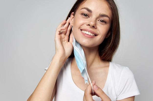 La mujer se pone una máscara en la cara sonrisa camiseta blanca primer plano fondo claro