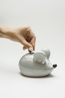 La mujer pone una moneda en la hucha de un ratón gris.