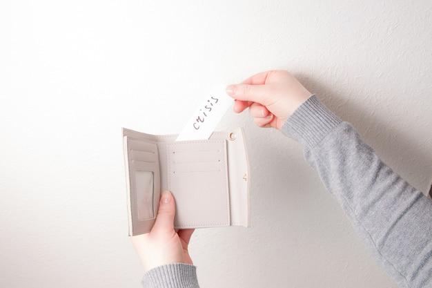 Una mujer pone un papel con la inscripción crisis dentro de una billetera