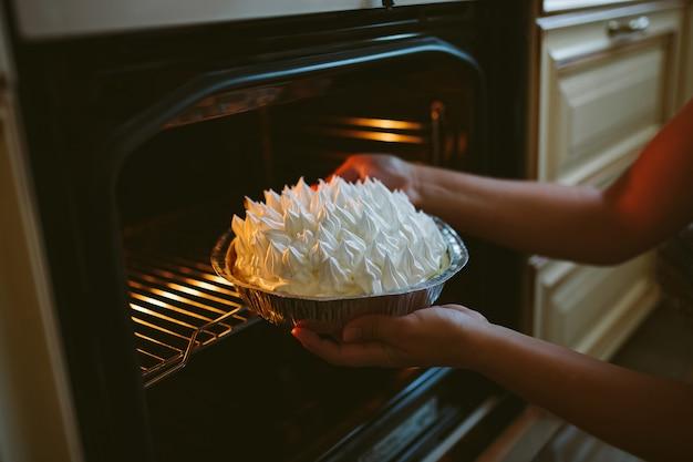 Mujer pone pastel en el horno