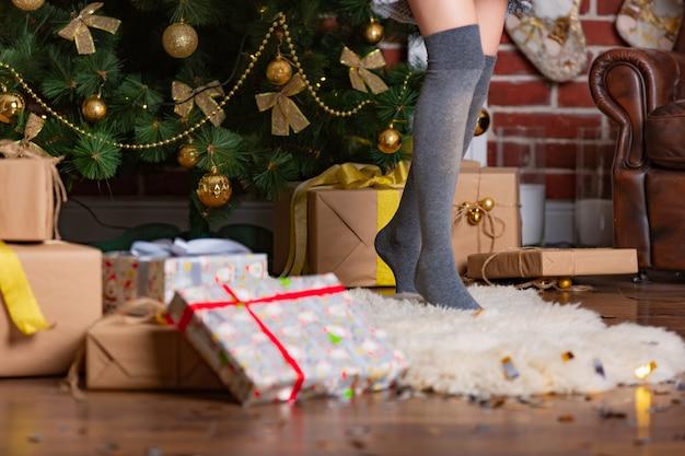 La mujer se pone de puntillas en una cálida polaina sobre una alfombra de piel en la habitación cerca del árbol de navidad con regalos