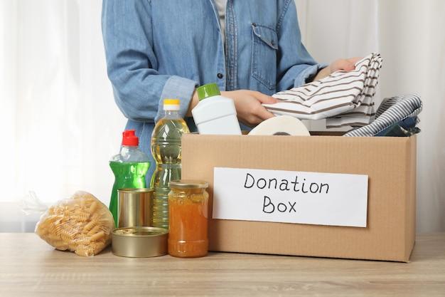 Mujer pone ropa en caja de donación en mesa de madera