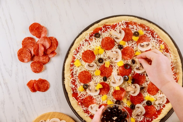 Mujer poniendo aceitunas en pizza cruda cruda.