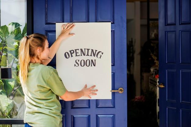 Mujer poniendo en la apertura de la tienda muestra pronto