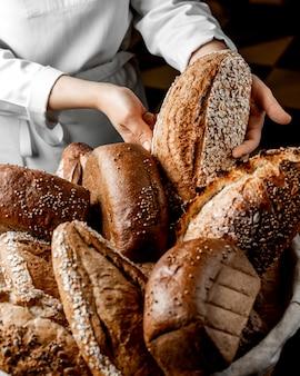 Mujer poniendo bollo de pan integral entre otros panes