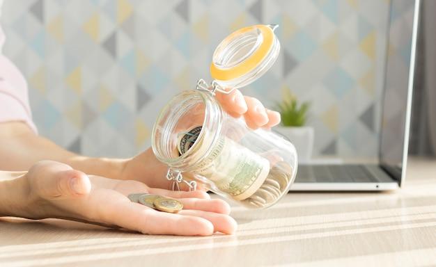 Mujer poniendo dinero en un frasco de vidrio en la mesa, primer plano