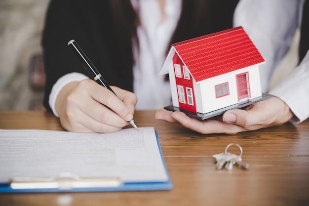 Mujer poniendo firma en contrato de préstamo de documento, bienes raíces