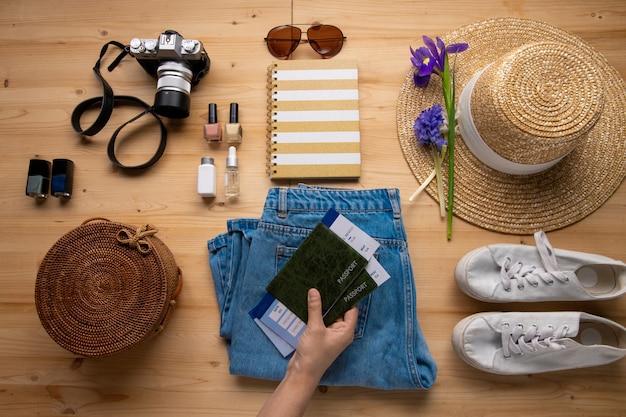 Mujer poniendo pasaportes con billetes de avión en jeans mientras se prepara para las vacaciones