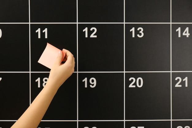 Mujer, poniendo, pegatina, a bordo, calendario, primer plano