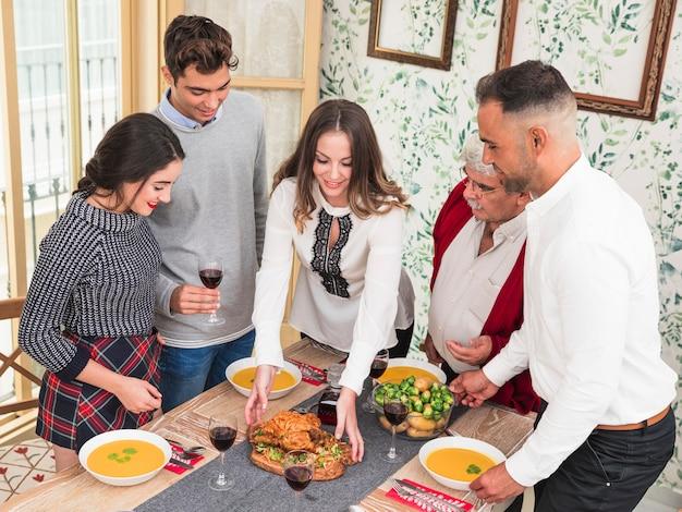 Mujer poniendo pollo al horno en mesa festiva