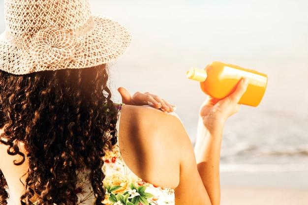 Mujer poniendo protector solar a orilla del mar