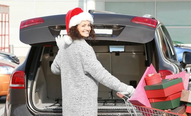 Mujer poniendo regalos en el maletero del coche al aire libre