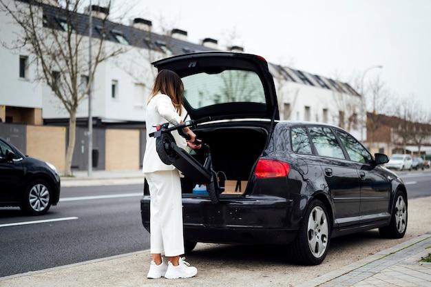 Mujer poniendo scooter eléctrico en coche