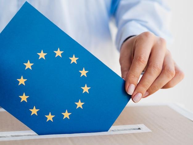 Mujer poniendo un sobre de la unión europea en una caja