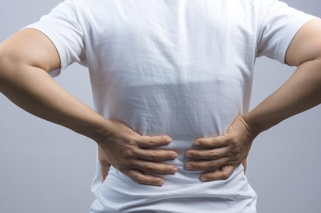 Mujer poniendo sus manos por dolor de espalda o columna vertebral