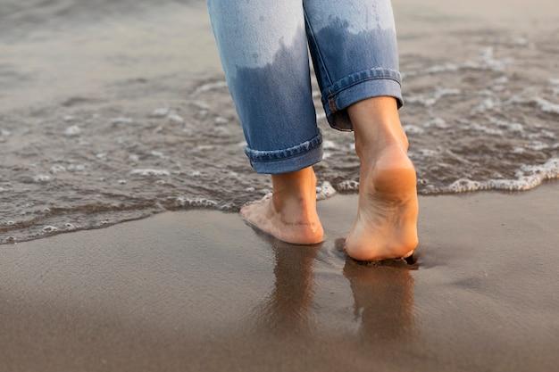 Mujer poniendo sus pies en el agua en la playa.