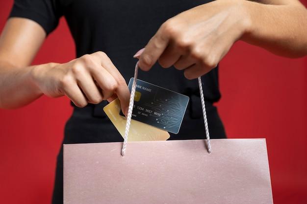 Mujer poniendo tarjeta de crédito en bolsa de compras