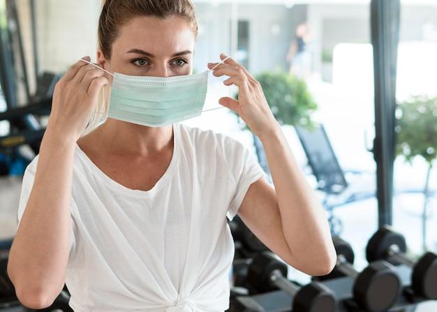 Mujer poniéndose máscara médica en el gimnasio