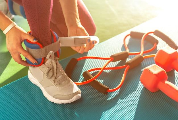 Mujer poniéndose pesas en los tobillos antes de comenzar un entrenamiento en un gimnasio, concepto de salud y estado físico con pesas en la estera