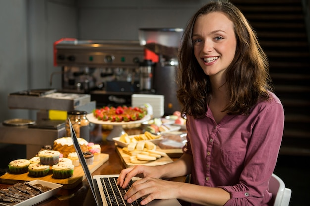 Mujer con portátil en el mostrador de panadería en el mercado