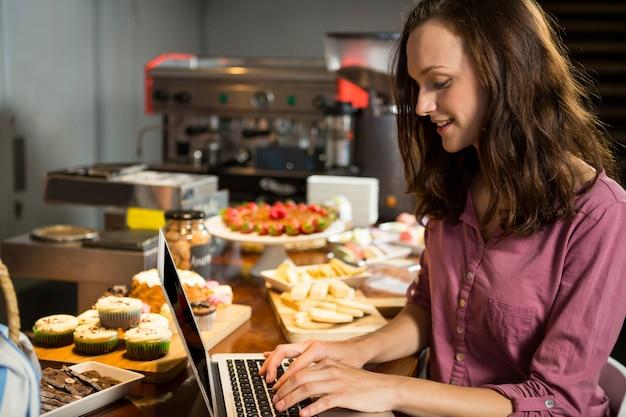 Mujer con portátil en el mostrador de la panadería