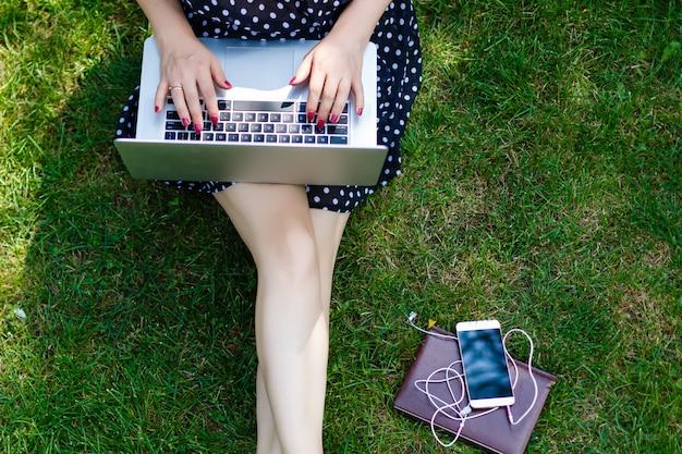 Mujer portátil sentarse hierba