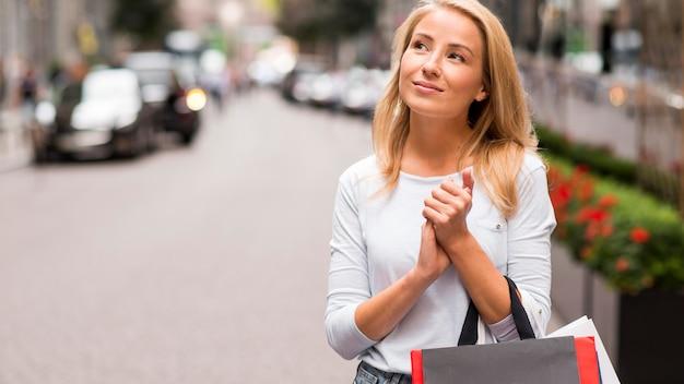 Mujer posando al aire libre sosteniendo bolsas de la compra.