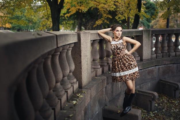 Mujer posando apoyada en una barandilla de cemento