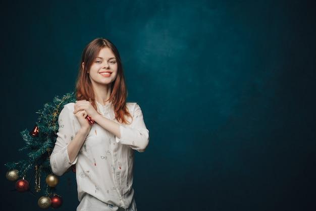 Mujer posando con árbol de navidad