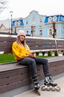 Mujer posando en un banco con patines