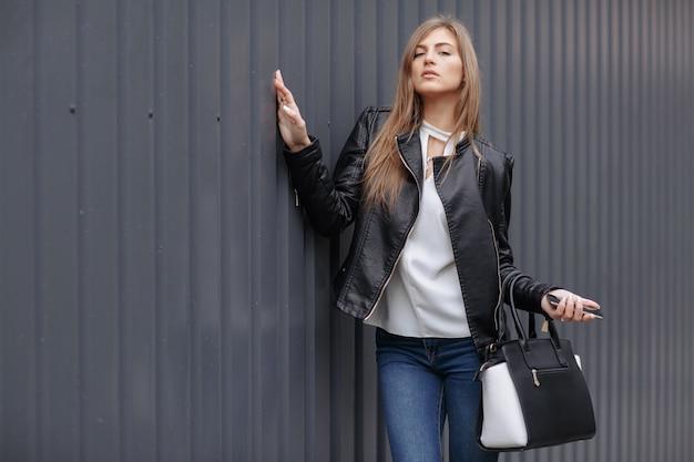 Mujer posando con un bolso negro y blanco