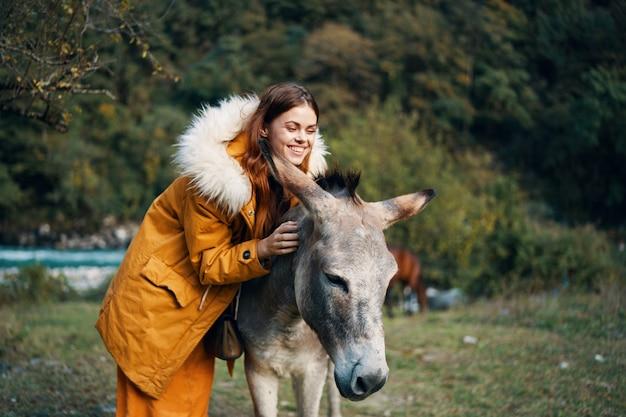 Mujer posando con un burro en la naturaleza en las montañas