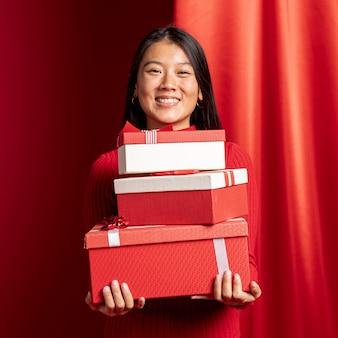 Mujer posando con cajas de regalo para año nuevo chino