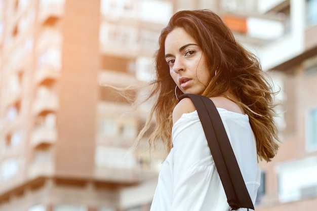 Mujer posando en la calle, en un bloque de apartamentos de fondo.