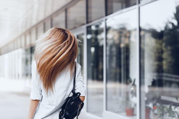 Mujer posando en la calle, sosteniendo una bolsa oscura