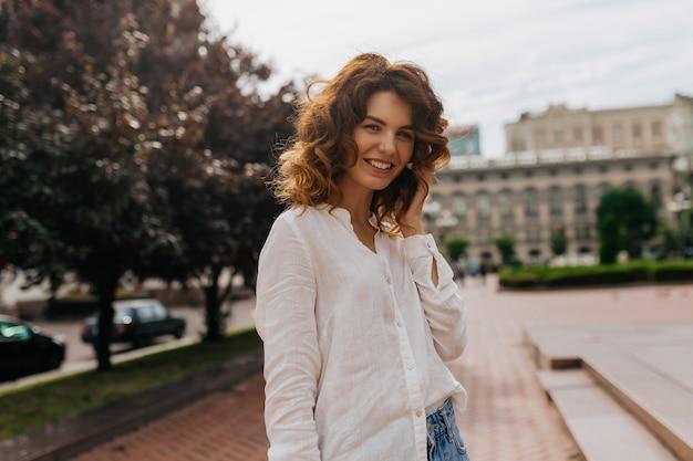 Mujer posando delante de edificios antiguos. mujer rizada emocionada con teléfono en mano posando al aire libre
