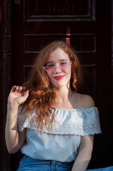 Mujer posando delante de una puerta con gafas de sol
