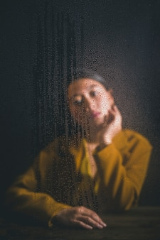 Mujer posando detrás de la ventana con gotas de lluvia en él