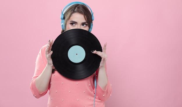 Mujer posando con disco de vinilo mientras usa auriculares