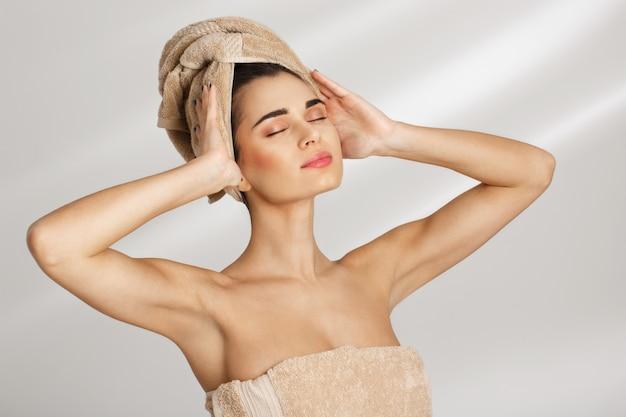Mujer posando con la mano en el hombro mirando hacia abajo. concepto de relajación.