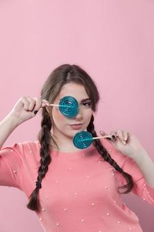 Mujer posando mientras cubría los ojos con piruleta