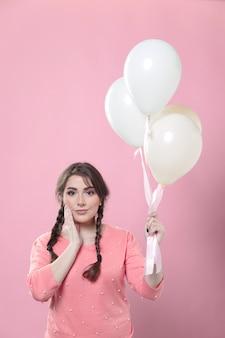 Mujer posando mientras sostiene globos