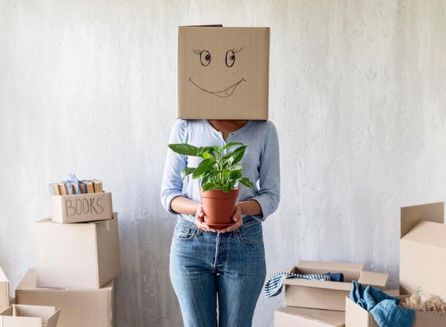 Mujer posando mientras sostiene la planta en la mano y la caja sobre la cabeza el día de la mudanza